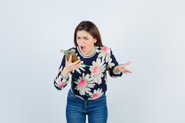 Giovane ragazza che tiene il telefono, dispiaciuta per la domanda stupida in camicetta floreale, jeans e guardando risentita, vista frontale.
