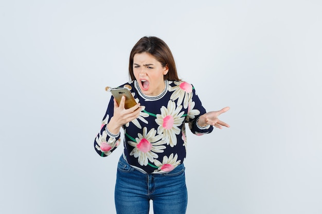 電話を持っている少女、花柄のブラウス、ジーンズのばかげた質問に不満を持って、憤慨している正面図を探しています。