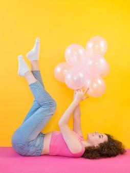 Молодая девушка держит розовые воздушные шары
