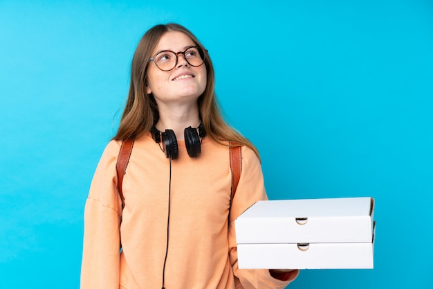 Young girl holding a pizzas boxes over blue background