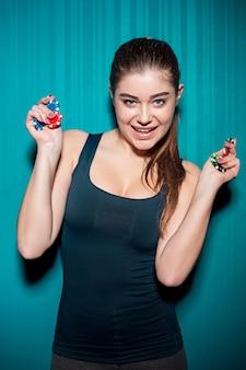 Молодая девушка держит фишки для покера на синей стене