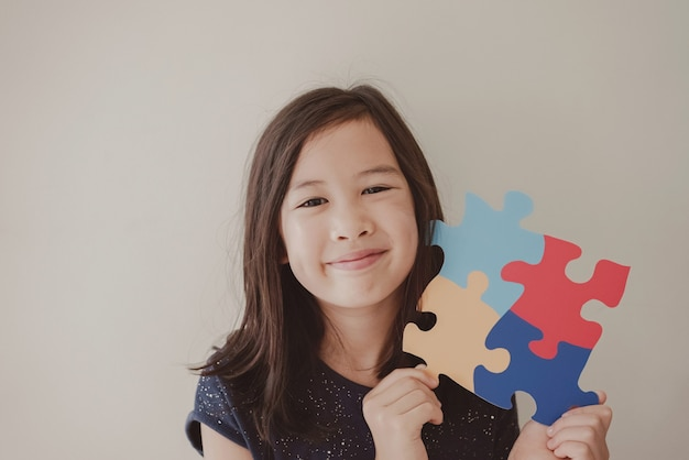 Young girl holding puzzle jigsaw,  child mental health , world autism awareness day