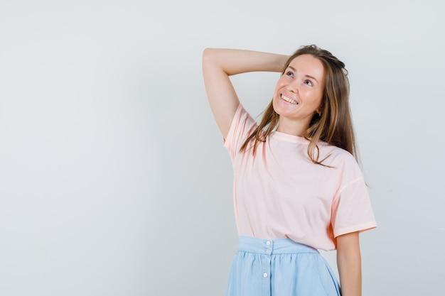 Tシャツ、スカート、希望に満ちた正面図で頭に手を上げた少女。