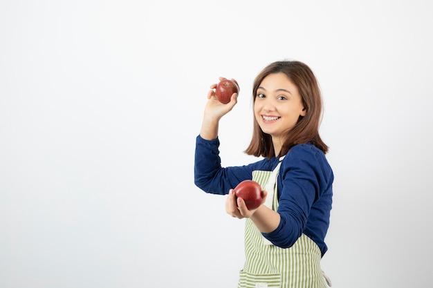 Giovane ragazza con mele rosse mentre sorride su bianco.
