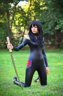 Молодая девушка держит самурайский меч. оригинальный косплей персонажа