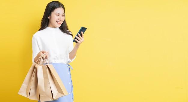 幸せな表情で買い物袋を保持している少女は黄色の背景に電話を使用しています