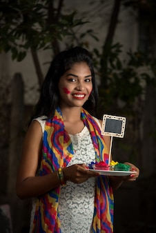 Young girl holding small board and powdered color on the occasion of holi festival.