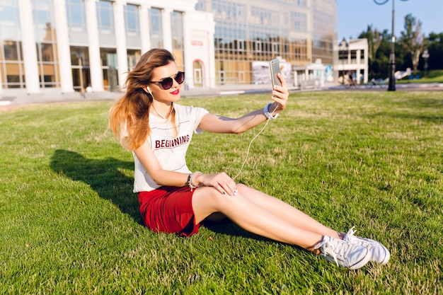 Young girl holding a smartphone and listening to music sits on the green grass in the city park