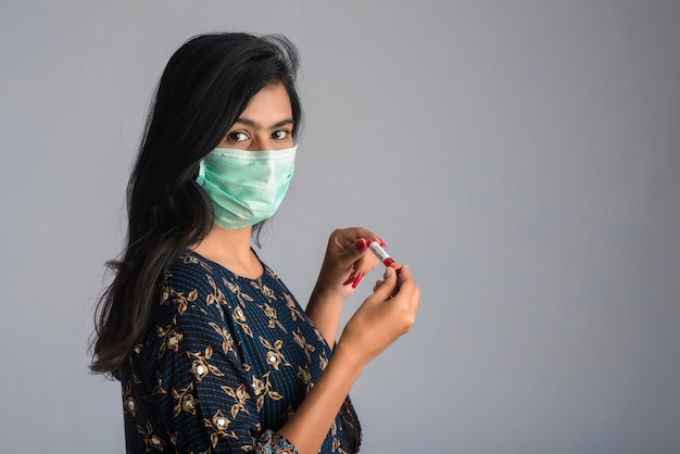 Young girl holding a test tube with blood sample for coronavirus or 2019-ncov analyzing.