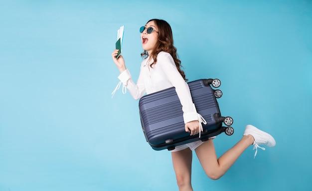 Молодая девушка держит билет на самолет, готовится к предстоящей поездке с веселым выражением лица