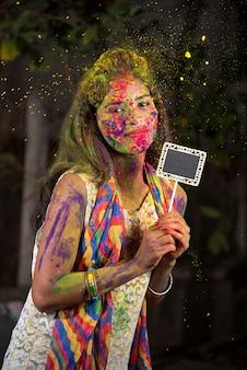 컬러 스플래시와 함께 가루 색상으로 칠해진 얼굴로 holi 축제 행사에 작은 보드를 들고 어린 소녀.