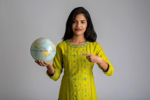 어린 소녀는 세계 세계를 잡고 회색에 포즈.