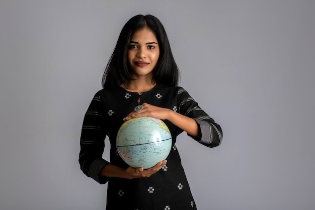 어린 소녀 세계 지구본을 들고 회색에 포즈.