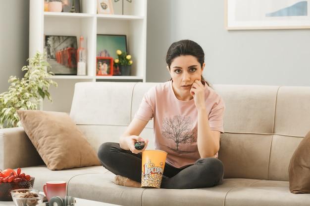 Молодая девушка держит пульт от телевизора, сидя на диване за журнальным столиком в гостиной