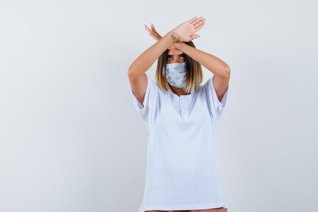 両腕を頭の上に交差させ、白いtシャツ、マスク、真剣に見える、正面図でサインを身振りで示す若い女の子。