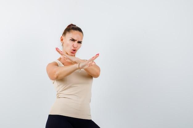 Giovane ragazza con due braccia incrociate, gesticolando nessun segno in top beige, pantaloni neri e guardando arrabbiato, vista frontale.