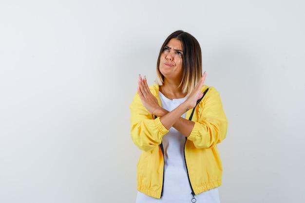 어린 소녀가 두 팔을 잡고 넘어, 몸짓, 흰색 티셔츠, 노란색 재킷에 입술을 휘감고 걱정, 전면보기를보고 있습니다.