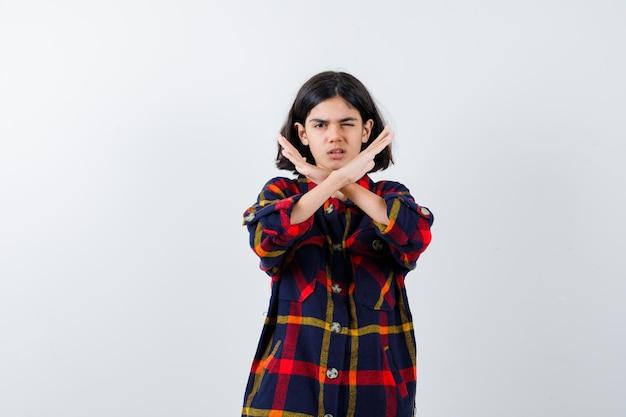 両腕を組んで、チェックのシャツにサインを身振りで示すことなく、真剣に見える少女、正面図。