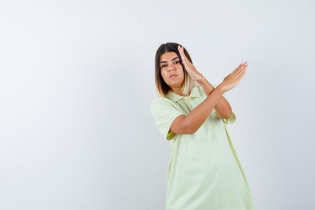 두 팔을 들고 어린 소녀 넘어, t- 셔츠에 흔적을 몸짓과 자신감, 전면보기를 찾고.