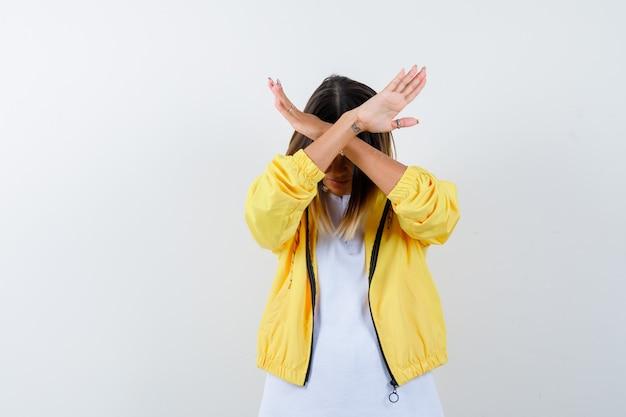 Молодая девушка держит две скрещенные руки, жестикулирует без знака в белой футболке, желтой куртке и выглядит раздраженным. передний план.