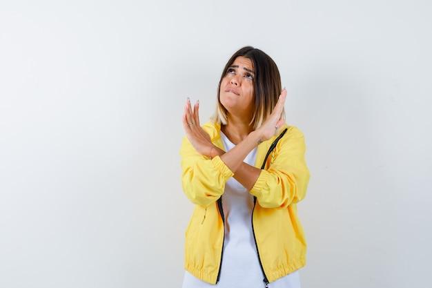 両腕を組んで、白いtシャツ、黄色のジャケット、心配そうに見える、正面図でサインを身振りで示す若い女の子。