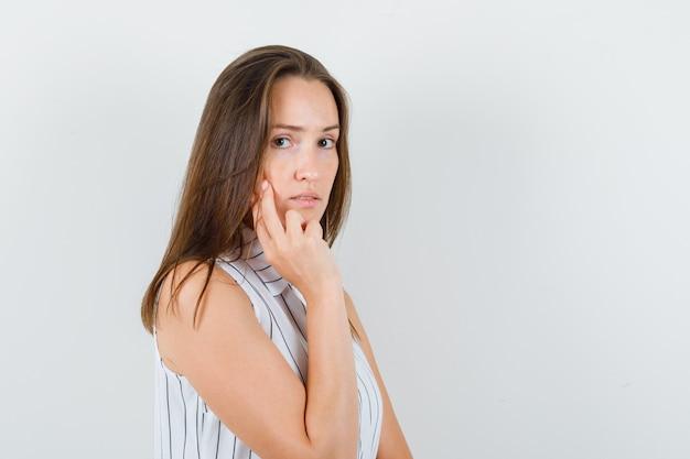 Tシャツの頬に2本の指を持って思慮深く見える少女。 。