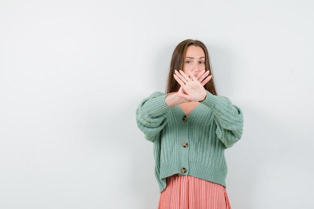 Giovane ragazza che tiene due mani incrociate, gesticolando x segno in maglieria, gonna e che sembra seria. vista frontale.