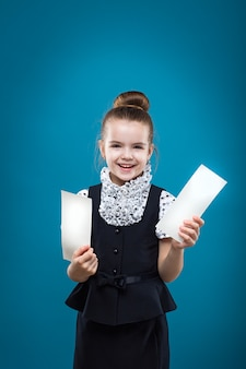 Young girl holding two papers and smiling