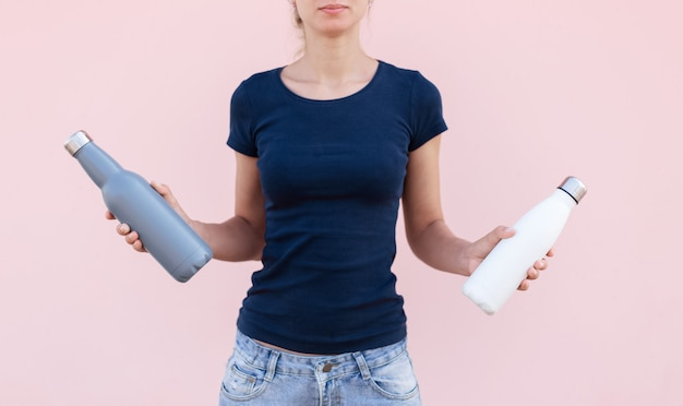 Young girl holding two reusable, steel thermo water bottles, white and grey of colors. pastel pink background. be plastic free. zero waste.