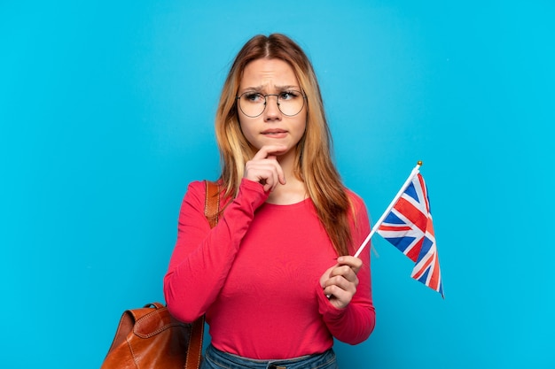 Young girl holding an united kingdom flag over isolated blue background having doubts and thinking