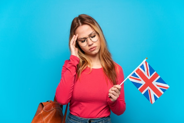 Young girl holding an united kingdom flag over isolated blue background with headache
