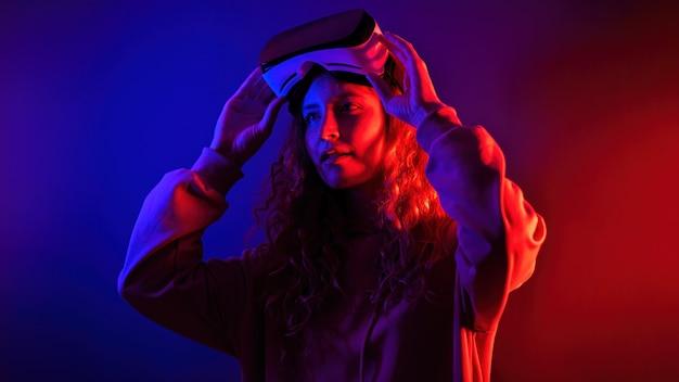 部屋の青と赤の照明で彼女の頭にバーチャルリアリティメガネを保持している若い女の子。自宅でのエンターテインメント
