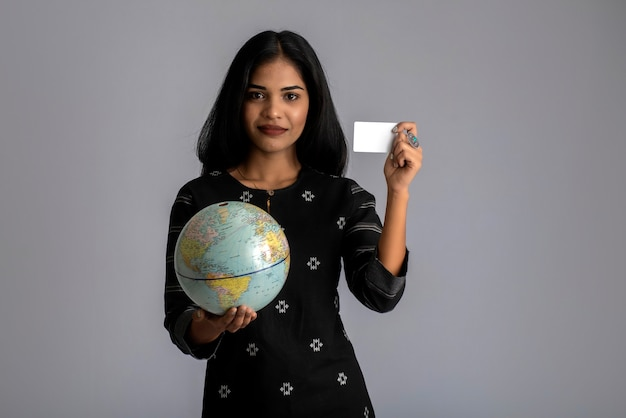 Young girl holding the world globe and posing with credit card on a grey wall.
