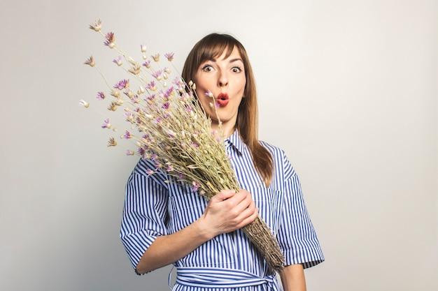 Молодая девушка держит букет полевых цветов, девушка показывает эмоции на светлом фоне