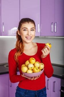 어린 소녀는 사과 그릇을 보유 하