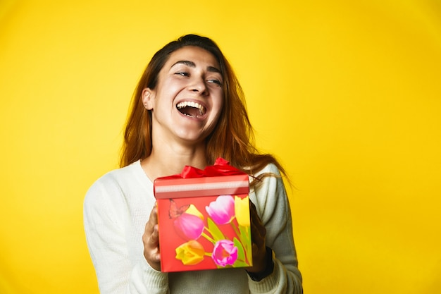 Молодая девушка держит подарок и имеет очень счастливый взгляд стоя