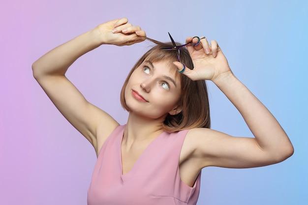 若い女の子は彼女の手にはさみを持って、散髪しようとしています
