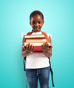 若い女の子は本を保持し、学校に行く準備ができて
