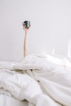 A young girl holds a cup of coffee on an outstretched hand in bed