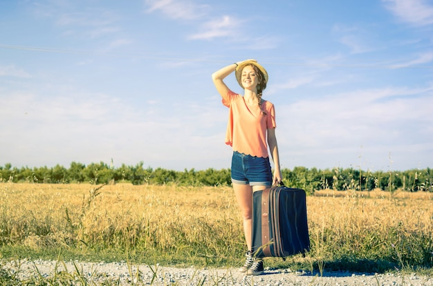 Young girl holds her suitcase in hand while smiling at vacation - people, holiday, nature and lifestyle concept