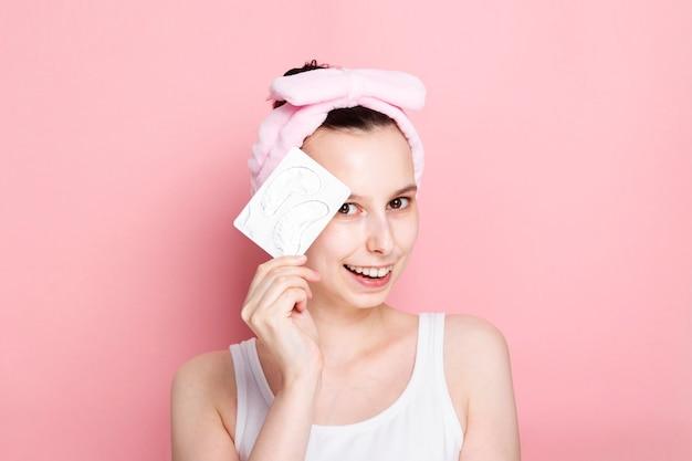 Молодая девушка держит в руках глазные пятна и улыбается на розовом пространстве