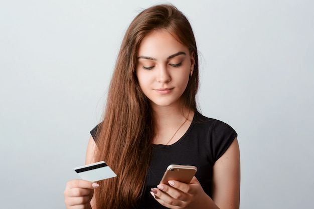 Young girl holds mobile phone and credit card