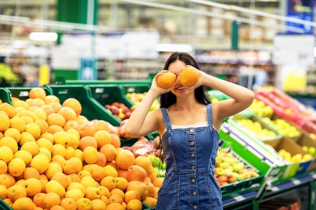 若い女の子は果物と棚の反対側に彼女の手でオレンジを保持します