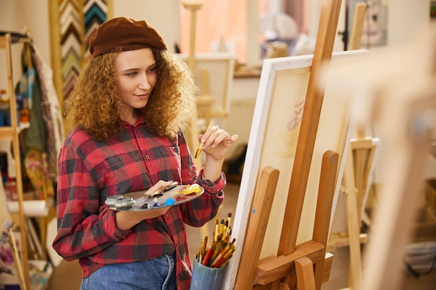 Young girl holds a palette with oil paints  and a brush