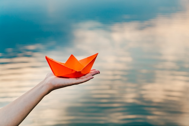 A young girl holds a paper boat in her hand above the river. origami in the form of a ship has an orange color