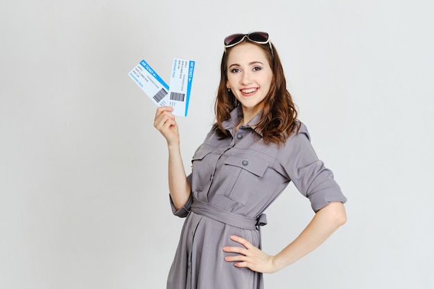 A young girl holds plane tickets on a white background as a travel concept.