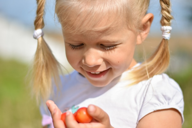 Young girl holds tasty red berries in her hand and laughs playing a summer day