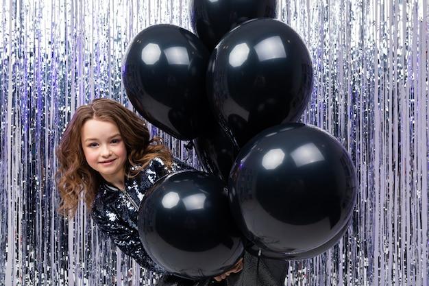 華やかなお祝い壁に風通しの良い黒いヘリウム風船で若い女の子を保持します