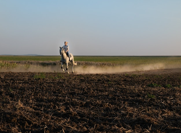 A young girl on horseback rides across the field during sunset.