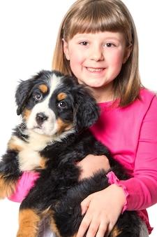 若い女の子はバーニーズマウンテンドッグの子犬を抱きしめます